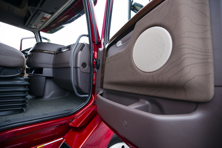 wood paneling: The interior of a modern luxury red semi truck made in shades of brown plastic. Through the open door with wood paneling truck visible part of the seat with shock absorbers and the dashboard console with air vents.