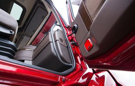 open car door: The interior of a modern luxury red semi truck made in shades of brown plastic. Through the open door with wood paneling truck visible part of the seat with shock absorbers and the dashboard console with air vents.