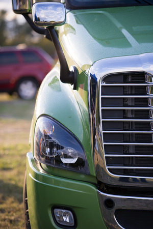 freightliner: Chrome grille headlight and fog lamp hood with fixed mirrors stylish powerful modern luxury comfortable green truck in the parking lot with reflection of light in the glare of paint on the back of a truck.