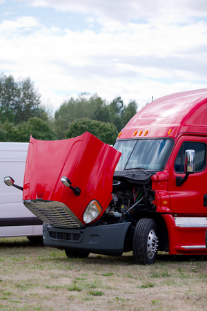 freightliner: Heavy Duty stylish modern red big rig semi - truck with an open hood to check condition the engine and the cooling system for the parking grassy field. Stock Photo