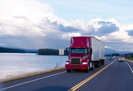 Red professional powerful truck with a spoiler and headlights pulling two trailers with cargo on a beautiful road along the quiet wide river with evening landscape.