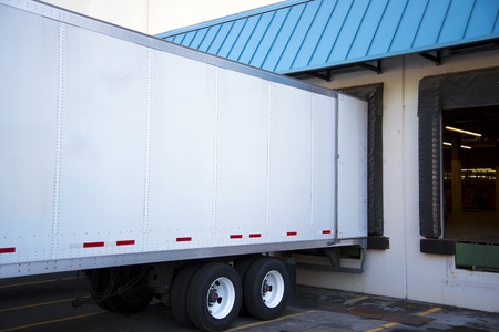docking: White long semi trailer with an open door stand close in the dock warehouse with a green sloping roof to unload or load cargo for delivery and transport to safety labels on the walls of the semi trailer.