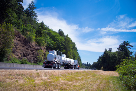 semitruck: Semi-Truck Big Rig with length tank transports hazardous substances regular flights with permission to transport on the highway in the beautiful scenic place Columbia Gorge with evergreen trees and mountain ranges.