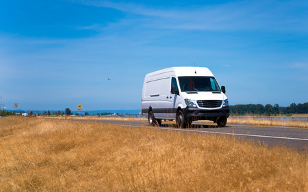 Small cargo van for local transportation and delivery of goods and parcels for business and private consumers on a straight flat road on the background of a large yellowed grass and blue sky.