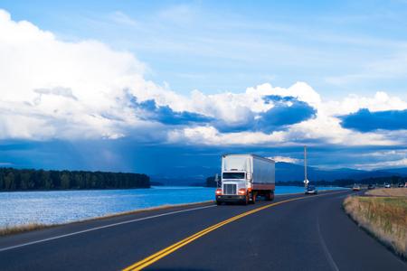 흰색과 주황색을 조합 한 세미 트럭과 트레일러는 푸른 흐린 하늘을 배경으로 강을 따라 경치 좋은 도로의 현지 장소로 물건을 배달합니다.