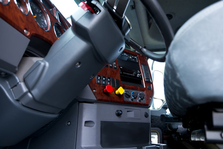 dash: Modern ergonomic and stylish dashboard of heavy semi truck with lots of equipment, Steering column, indicators, buttons, and other electronics, decorated with plastic imitation wood, integrated into the interior of a large commercial truck cab.