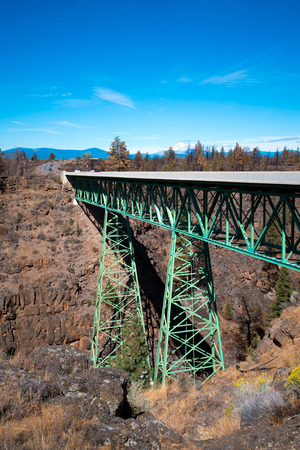 sparingly: Smooth straight metal bridge constructed of triangular trusses and truss mounted on two poles painted green along which the highway connecting the two walls rocky gorge, overgrown with sparingly trees. Stock Photo