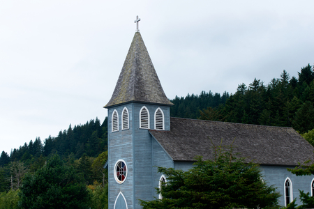 midst: Small rural provincial church without architectural excesses in the tower and a pointed dome with a cross and Gothic windows with stained-glass windows in the midst of evergreen trees that surround the church.