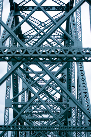 interweaving: Interweaving metal truss bridge forming geometric shapes squares and triangles stretching into perspective and woven into the web of the long bridge construction. Stock Photo