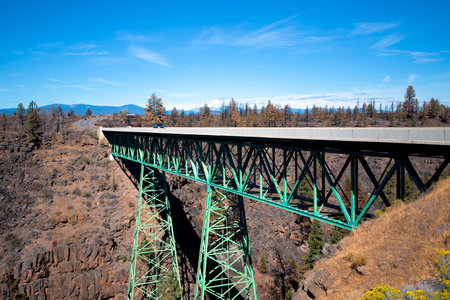 connection connections: Green metal truss road bridge on two conical truss supports poles abutting the bottom of a deep canyon formed between two rocky mountain ridges. The bridge is covered with concrete slabs of the road on which the moving car.
