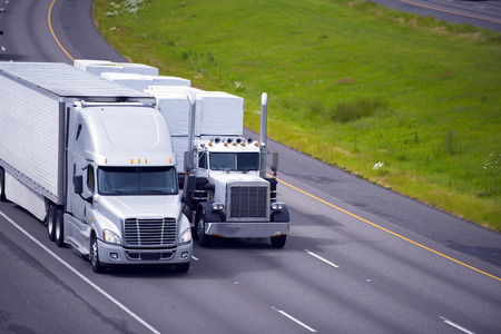 freightliner: Two heavy big rigs semi trucks of various types and models with different trailers and various cargoes rapidly moving close together on the international highway.