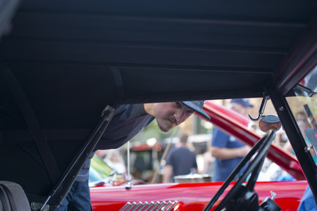 rarity: A man in a cap looking the interior of the restored old rarity retro red car with folding roof on the exhibition of luxury vintage cars on display in a row on street in the city with many visitors on this town holiday. Stock Photo