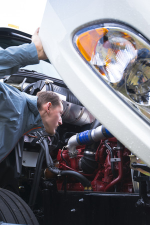 Male truck driver in a gray jacket inspects engine components on a semi truck with an open hood, checking it to make sure that all components and systems are working properly and the truck will not create problems on commertial cargo route.