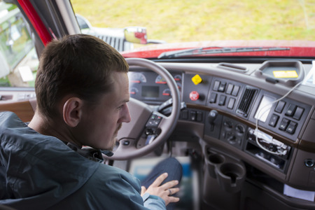 The truck driver sitting in the cab of modern comfort and ergonomic semi truck behind the wheel and interior dashboard with numerous control buttons and switches. The driver of semi truck assessment the situation, looking in the right rearview mirror. Archivio Fotografico