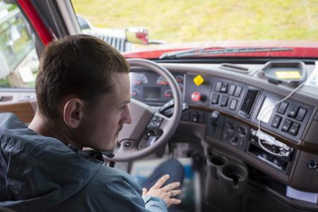 ciężarówka: Kierowca ciężarówki siedzi w kabinie nowoczesnego komfortu ergonomicznego Semi Truck za kierownicą i deską rozdzielczą wnętrz z wieloma przyciskami sterującymi i przełączniki. Kierowca ciężarówki pół oceny sytuacji, patrząc w prawym lusterku. Zdjęcie Seryjne