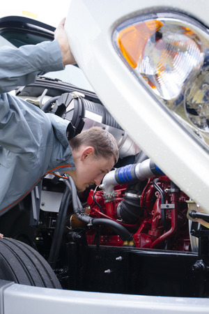truck engine: The professional Truck driver inspect his heavy semi truck engine to check the correct operation of all engine components before leaving for the next freight to deliver cargo to the United States or Canada.