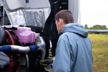 The truck driver checks the engine of his huge modern powerful big rig semi truck parked in the parking lot with an open hood and washed clean cooling systems components and lubricants.