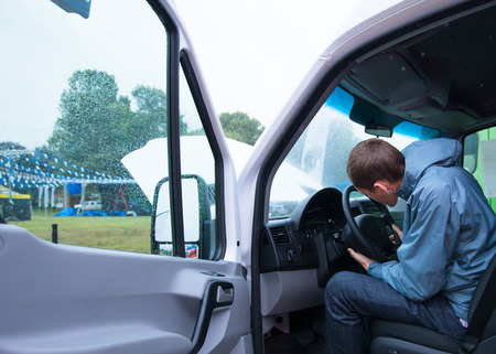 open car door: The driver adjusts the steering column in a cargo van with plastic trim open door and cabin interior. Van stay in parking lot and getting ready to drive on the road for work projects. Stock Photo