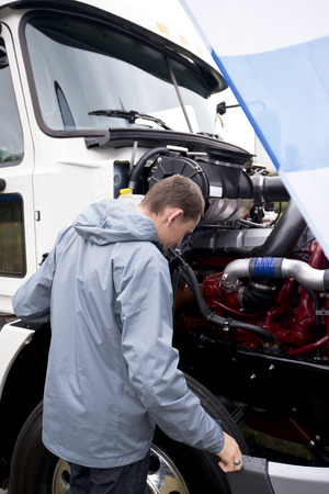 Truck driver in a gray jacket with a hood checking the operation status of the components of the engine under open hood of white modern heavy semi truck, standing in the parking lot to check before going on the road for the delivery of industrial goods.