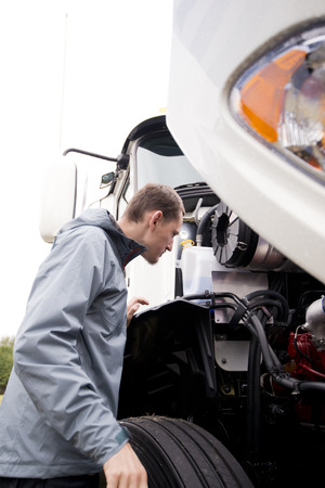 Professional truck driver checks the status of his steel horse with a diesel engine under the open hood of a huge modern semi truck regulations specification verification of technical control of transport services and manufacturers.