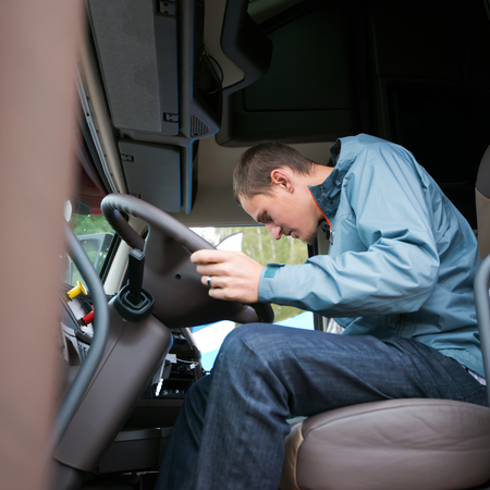 truck driver: Young man truck driver sits in a comfortable cabin of modern truck and check the readiness of the truck electronics systems for use on the highway when transporting cargo. Stock Photo