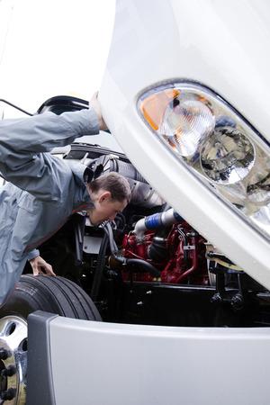 camion: Profesional joven examen de conductor de camión de la situación de su semi camión con un motor diesel bajo el capó abierto de una enorme base de camión semi moderna en la verificación especificaciones normativas de control técnico de los servicios de transporte y fabricantes. Foto de archivo