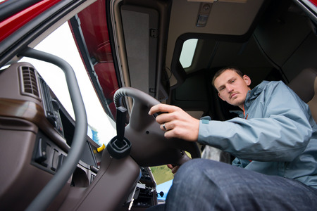 A young truck driver behind the wheel of modern comfortable cab of the big rig semi truck with a high cabin and open the door ready to start moving to the point of loading.