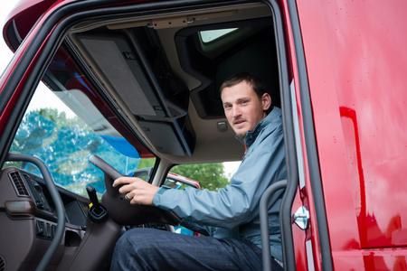 profesionistas: conductor de camión feliz que se sienta en la cabina del camión rojo detrás del volante y mirando a través de la puerta abierta. El camión semi moderno está ubicado en la playa de estacionamiento y el conductor está listo para pasar a la siguiente viaje. Foto de archivo