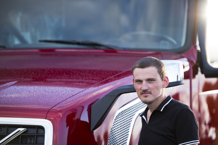 truck driver: A young truck driver involved in professional freight over long distances, stands next to his contemporary popular red semi truck, ready to start driving  this big rig.