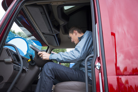 Truck driver on the steering wheel of modern comfortable cab of the semi truck and the truck is ready to operate on the road and checks the condition of the navigation system.