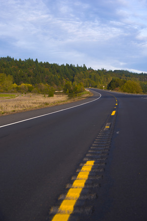 audible: The broad highway that goes to a point on the horizon, with yellow dividing strip and grooved recesses audible warning when hitting for road safety and green forest on the horizon. Stock Photo