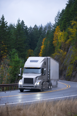 Modern professional long haul heavy semi truck with lights on and trailer for long distance transporting at the turn of the winding scenic highway with autumn trees on the rocks in the rain.