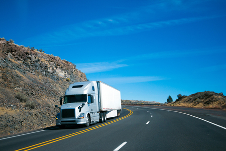 Modern long haul commercial cargo pro power silver big rig semi truck with trailer and aerodynamic to save fuel at the turn wide multilines highway among the rocky hills flanking the road.