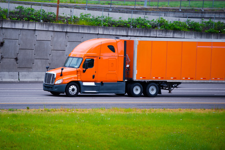 Modern long haul commercial cargo pro power bright orange big rig semi truck with trailer and aerodynamic to save fuel at the staight wide multilines highway among the rocky concrete wall flanking the road.