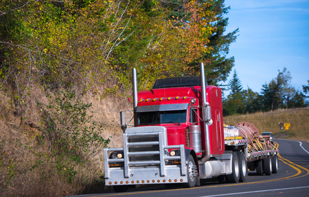 Powerful heavy huge bright red professional classical big rig semi truck with a thick protective grille and high tailpipes and step-down trailer where the straps tied several pallets load at the turn of autumn winding road. Imagens