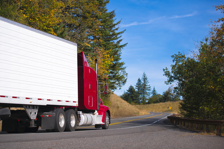 haul: Classic red big rig long haul semi truck transporting cargo in refer trailer on a beautiful autumn winding devided road highway with yellow leaves on the trees. Stock Photo