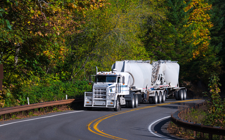 Big contrast white stylish powerful professional rig semi truck with a protective grille and two trailers for bulk cargo moves along lane winding highway among yellowed autumn trees.
