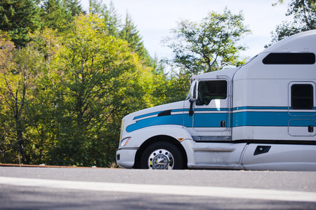 Powerful eagle profile of a huge long haul semi truck - eagle with a high roof and a sleeping compartment carries cargo in the scenic highway with green trees and the solar atmosphere on the road.
