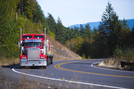 Muzzle classic red semi truck with a chrome grille and vertical exhaust pipes with flat bed trailer loaded with pallets commercial cargo on a bend of the meandering highway surrounded by lush green trees in the hills.