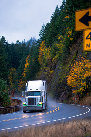 Spectacular powerful semi truck with a trailer at the turn of the winding road passing among the rocky mountains covered yellow and green autumn trees in the rain cloud of dust of the water under the wheels and the reflection of the lights on the wet road Zdjęcie Seryjne