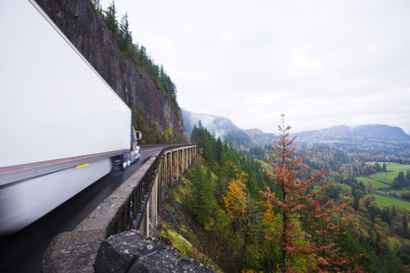 Impressive panorama of the valley of the Columbia River Gorge in the fall season with a huge long haul cargo semi truck with a dry van  trailer moving at high speed on the overpass, built on the slope of the cliff, along which the scenic highway.