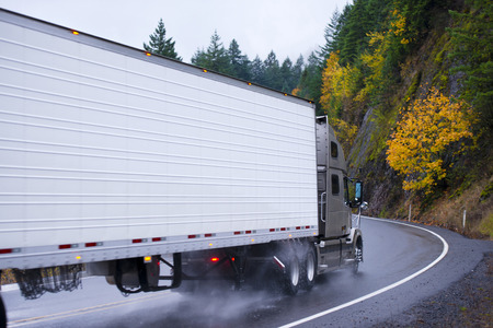 Spectacular powerful semi truck with a reefer trailer at the turn of the winding road passing among the rocky mountains covered yellow and green autumn trees in the rain cloud of dust of the water under the wheels and the lights on the white wall of the t