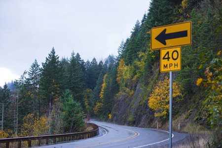 behold: Winding scenic road in the rainy autumn shiny from the rain among the rocks, covered with autumn trees and road sign with the direction arrow and safe travel speed. Stock Photo