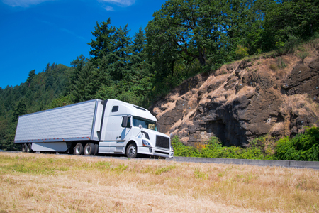 White modern long haul semi truck and refrigerated trailer with a refrigeration unit moving highway along the past the rocks and green trees.