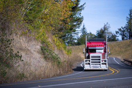 Powerful bright stylish popular professional red big rig semi truck with a protective grille from running out into the road animal, semi truck goes on a winding road with devided yellow lines and autumn trees.
