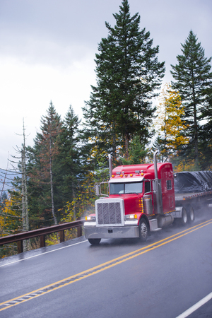 Big red semi truck classic American style with traditional tailpipes and other chrome accents and flat bed trailer on which are transported Industrial goods covered with black cover moves along a mountain road in the rain on a background of autumn trees a