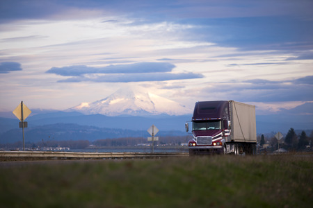 Dark professional semi truck with trailer transporting commercial goods on the scenic road with a metal security fence on the background of snow-capped Mount Hood and a dark cloudy sky. Imagens