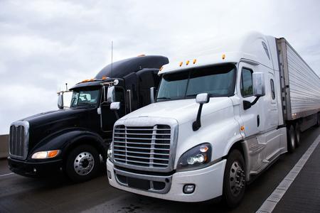 Dwie kontrastujące błyszczące nowoczesne czarno-białe duże wiertnicze naczepy Samochody ciężarowe o przyczep i wysoką kabiną sypialną dla kierowców ciężarówek relaks na stronie Fani boku wzdłuż autostradzie przewożących towary handlowe. Zdjęcie Seryjne