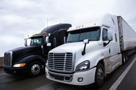 grill: Two contrasting shiny modern black and white big rigs semi trucks with a trailers and a high sleeper cab for truckers relaxing on truck stop move side by side along the interstate highway carrying commercial goods.