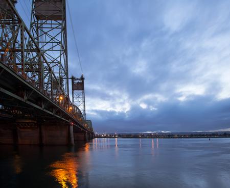 part of me: Levantando puente de armadura con torres de elevación a través del río Columbia en Portland en la noche con las luces del puente se refleja en el agua. El puente conecta Oregon y Washington y es parte de un camino de la carretera interestatal I-5. Foto de archivo